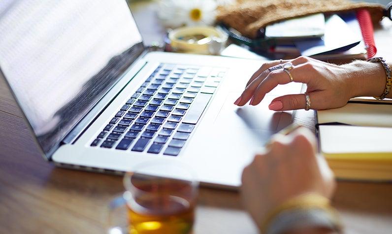 La mano de una mujer escribiendo en una computadora.