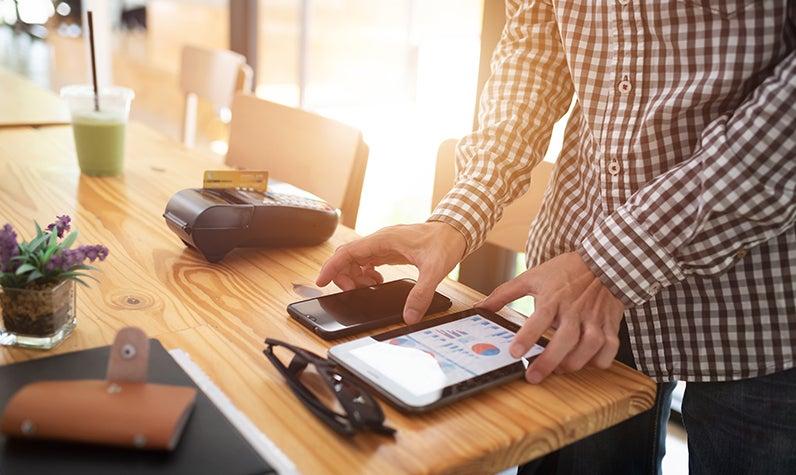 Un hombre arreglando sus finanzas en dispositivos móviles.