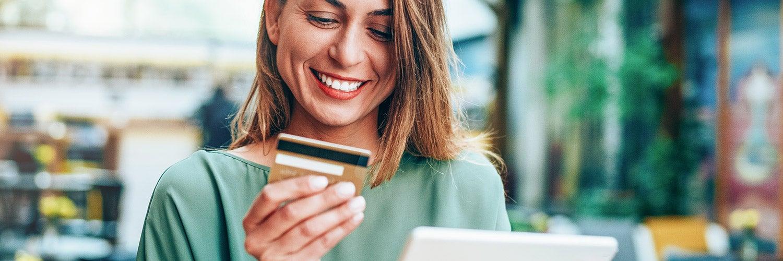 Una mujer mira su tarjeta de crédito.